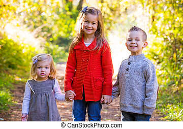 Three Young Siblings - Three children stand together...