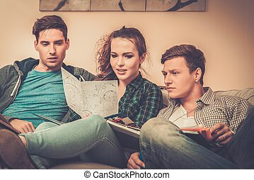 Three young students preparing for exams in apartment...