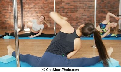 Three young woman doing exercises in a studio. Side slopes....