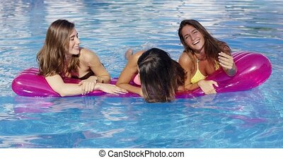 Three young woman floating on an air mattress laughing and...