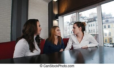 Three young woman in the hookah place talking to each other