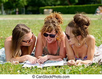 three young woman on the beach reading a magazine