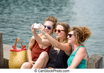 three young woman on the beach with their phone