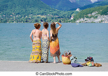 Three young women at the waterfront of lake