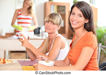 Three young women having breakfast at home