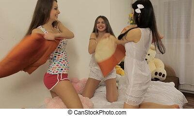 Three young women having fun (pillow fight)
