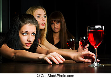 Three young women in a night bar - Three young women...