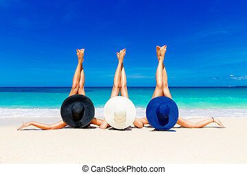 Three young women in straw hats lying on a tropical beach,...