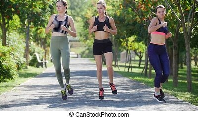 Three young women jogging in the park in summer