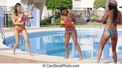 Three young women playing with colorful water guns - Three...