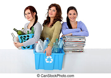 Three young women recycling