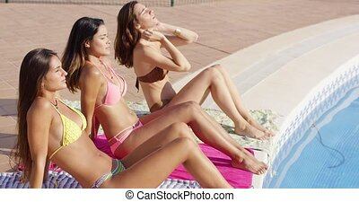 Three young women sun tanning in bikinis at the edge of a...