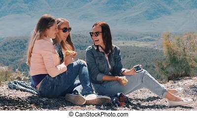 Three young women taking selfie with mobile phone