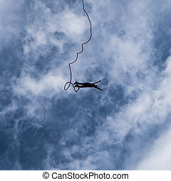 A thrill seeking bungee jumper falling to the ground.