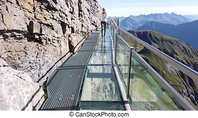 Outdoor activities in Birg, 2677, on Schilthorn in Bernese Prealps, Canton of Bern, Switzerland. Happy tourist woman walks the Thrill walk on a crystal floor suspended above village of Murren.
