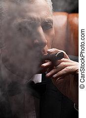 Through a cigar smoke. Close-up of confident mature man...