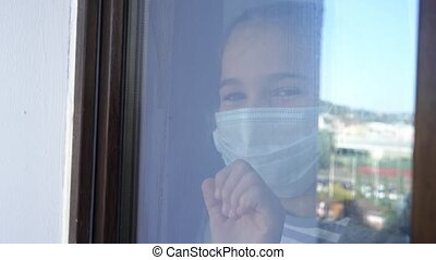 through the glass. a happy teen girl in a protective mask, look out of the window outside. she was ill and is recovering. self-isolating during the pandemic.