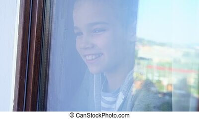 through the glass. a happy teen girl look out of the window outside wave his hands, meets parents. she is recovered and self-isolating during the pandemic. distance learning.