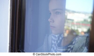 through the glass. a sad teen girl look out of the window outside. she is sick and self-isolating during the pandemic. distance learning.