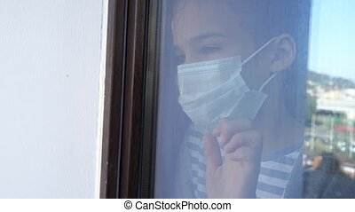 through the glass. a teen girl in a protective mask, look out of the window outside. she is sick and self-isolating during the pandemic.