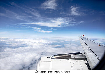 through plane window with beautiful white cloud and blue sky