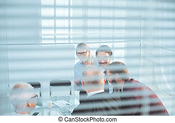 through the blinds. business team discussing business issues