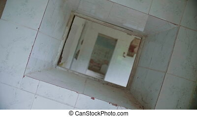 Through the hole in the wall of abandoned building, rotated...