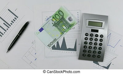 Throw euro on the chart with calculator and pen. Throwing Money down table.