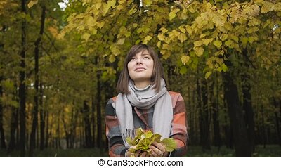 throw in the top yellow leaves. Autumn girl walking in city...