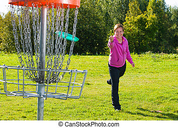 Throwing a disc - Woman throwing a disc to the disc basket