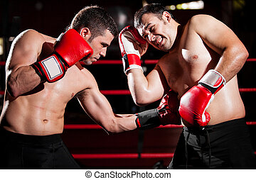 Throwing a hook on a boxing fight - Latin boxer punching his...