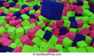 throwing blue cube into pit in amusement center - throwing...