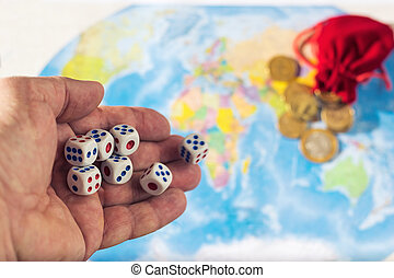 Throwing dice on a map of the world with a bag of coins. World order. d map and money