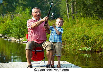 Throwing fishing tackle - Photo of grandfather and grandson...