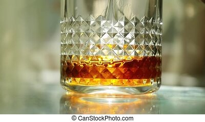 Throwing ice cubes in a glass of whiskey in slow motion