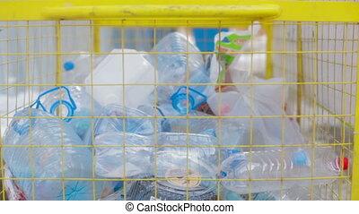 Throwing plastic waste to recyble bin - Hand giving plastic...