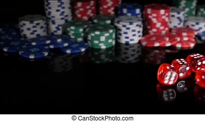 Throwing red dice on the background of poker chips. 3 pack. Slow motion.