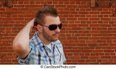 thug guy hooligan in black glasses looks into the camera on the background of a brick wall, close-up, slow-mo, outrageous
