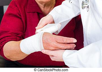 Thumb bandaging - Photo of doctor bandaging the elderly...
