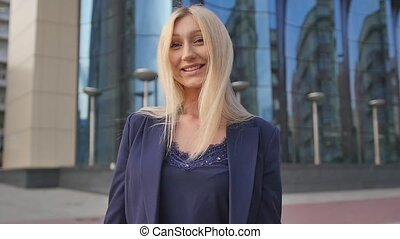 Thumb up. Happy young beautiful blonde at work, looking into the camera. Young woman showing like sign with hand. Portrait of a business woman. Positive girl shows thumb up gesture. Slow motion
