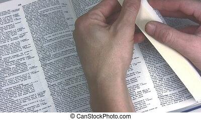 Thumbing through a dictionary - Hand thumbing through the...