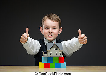 Thumbing up little boy with home model and blocks
