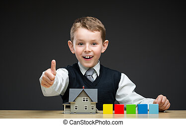 Thumbing up little boy with house model and blocks