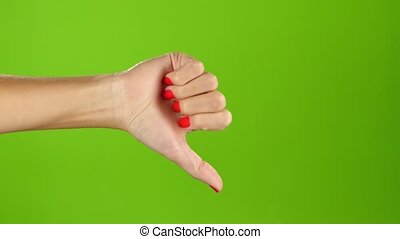 Thumbs down female hand on green screen background, gestures and body language, right hand, fingernails are covered red nail, hand appears in frame on the left side, nude female hand