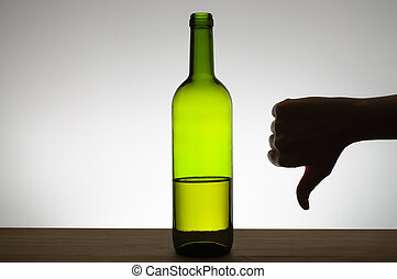 Silhouette of a hand showing thumbs down gesture next to a bottle of wine