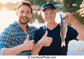 Thumbs up. A man stands next to an old man who is holding a fish he has just caught