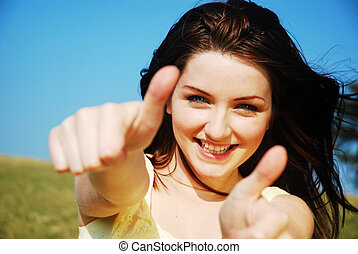 Thumbs up! - Beautiful young woman giving a thumbs up and...