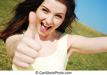 Beautiful young woman giving a thumbs up and smiling in a field with a blue sky.