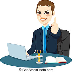 Successful businessman making thumbs up hand sign in front of his desk while working typing on laptop