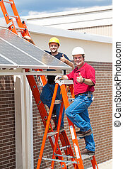 Thumbs Up for Solar Energy - Two workers installing solar...